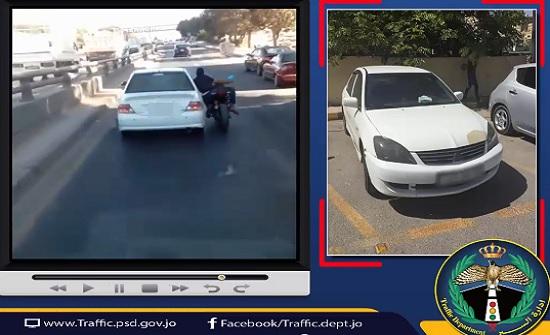 ضبط سائق مركبة تعلق بها شخص يقود دراجة نارية - فيديو