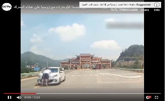 امرأة تقود السيارة وزوجها متشبث بغطاء المحرك في الصين