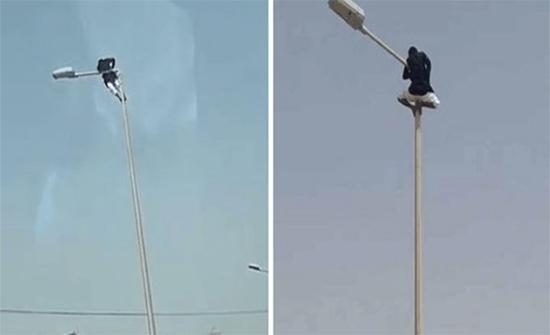 شاهد: طالب يتسلق عمود إنارة ارتفاعه 15 متراً ويتأرجح عليه في السعودية