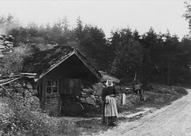 Äldre_kvinna_framför_backstuga_(jordstuga)_-_Nordiska_Museet_-_NMA.0051913
