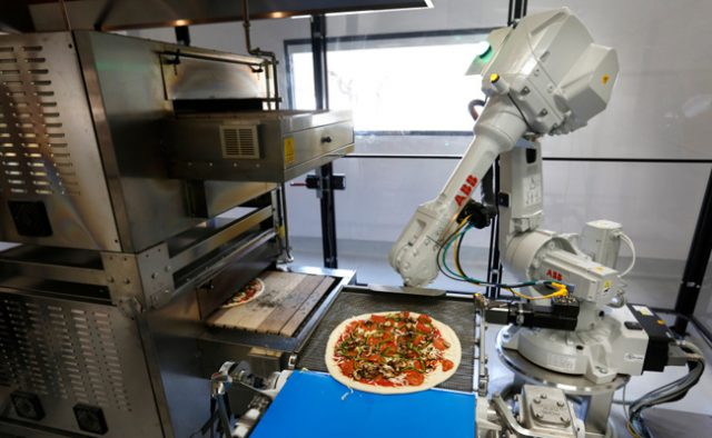 A robot places pizzas into an oven as it comes off a conveyer belt at Zume Pizza in Mountain View, Calif., Wednesday, Aug. 24, 2016.  Zume Pizza uses robots to make customers' pizza, hoping to reduce labor costs and therefore make pizza a more profitable venture. One robot spreads the sauce on the uncooked pies, then humans add toppings, and another robot pops it in the oven. They are also hoping to use delivery trucks with smart ovens to cook pies en route to customers. (Patrick Tehan/Bay Area News Group)