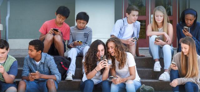Teenagers using their phones during school break