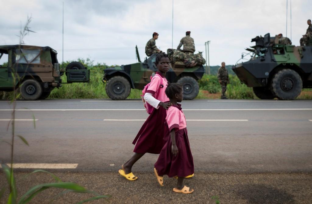 Kinderen lopen over straat, met op de achtergrond Franse militairen.