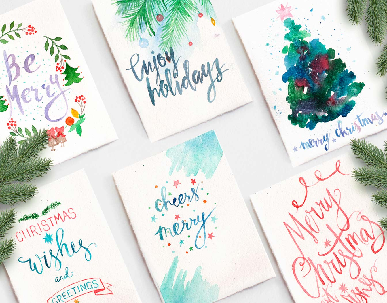 Watercolor Christmas cards lined up on white surface