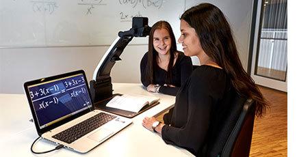 BIld på ung kvinna som sitter vid en dator kopplad till läskameran MagniLink PRO som förstorar texten i boken hon har lagt på läsbordet.
