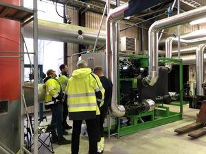 Bild på personer som står och tittar på en ORS-turbin i fjärrvärmeverket i Moheda.