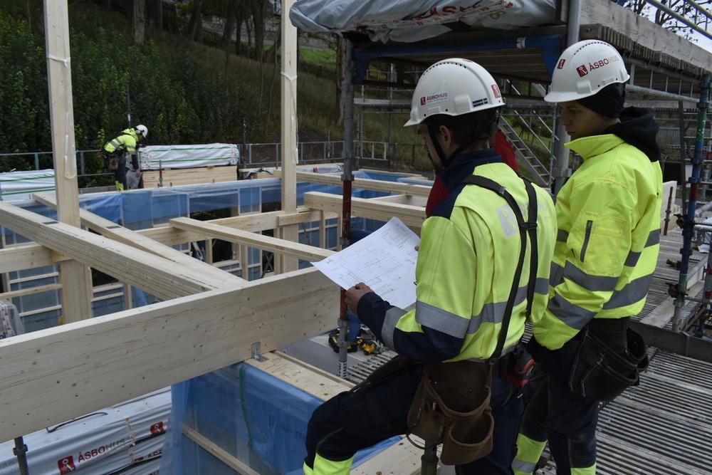 Två byggare står och tittar på husritning inför bygge