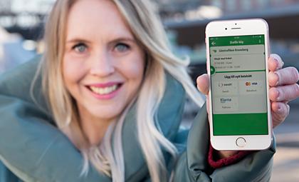 Illustrativ bild: Blond kvinna håller upp en smarttelefon. Telefonen visar ett utsnitt av vår reseapp.