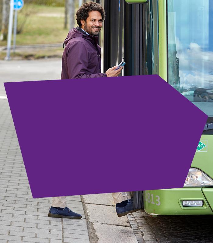 En man med lila jacka och mörkt lockigt hår stiger på en stadsbuss. Han tittar in i kameran och ler. Han håller en mobiltelefon i handen.