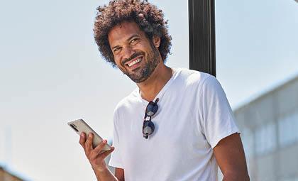 På bilden syns en man i vit tröja. Han ler. Håller sin mobiltelefon i högra handen.