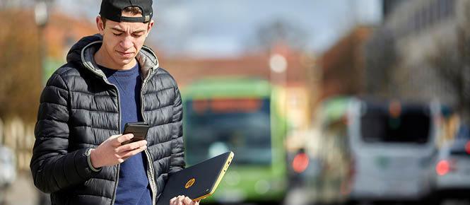 Kille står och väntar på en stadsbuss. Han har på sig en svart tunn dunjacka, svart keps med skärmen bakåt och håller en bärbar dator under ena armen. Han tittar ner i en telefon som han håller i sin högra hand.