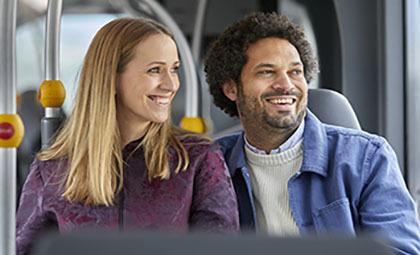 På bilden syns en kvinna och en man. Både kvinnan och mannen sitter ner i en buss. De båda ler och kollar ut i fönstret.