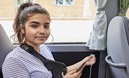 På bilden sitter en tjej i en buss. Hon håller i ena handen sin mobiltelefon och i den andra en sladd att sätta in i uttag. Hon sitter längsmed fönstret.