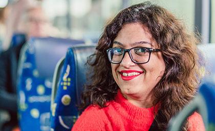 Bild på en kvinna som sitter i en buss. Hon ler.