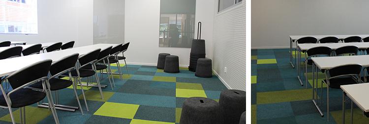 Foto på mötesrum Curie med färgglatt golv, vita bord och svarta stolar.