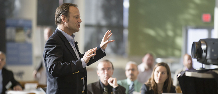Foto på en man som pratar framför en publik och en kamera.