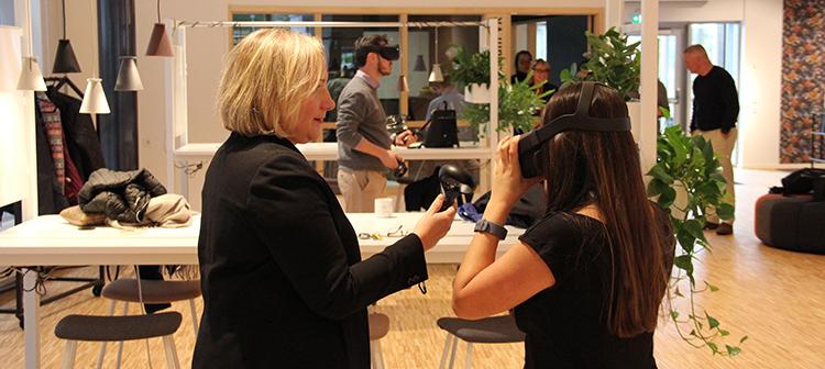 Foto på en kvinna som instruerar hur man använder headset för virtual reality.