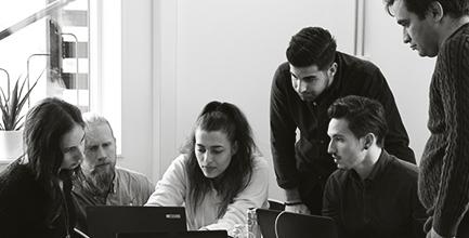 Ungdomar som jobbar tillsammans framför en dator.
