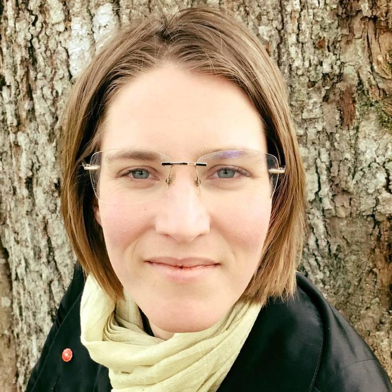 Projektledare Ingela Eriksson i grön sjal och svart jacka framför ett träd.