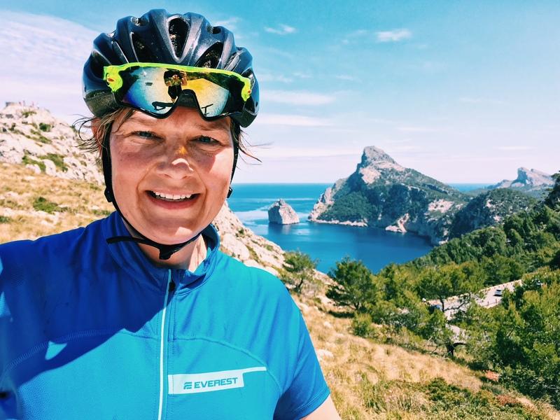 Porträttbild tagen i brösthöjd. Kvinna i cykelhjälm med hav och berg i bakgrunden.