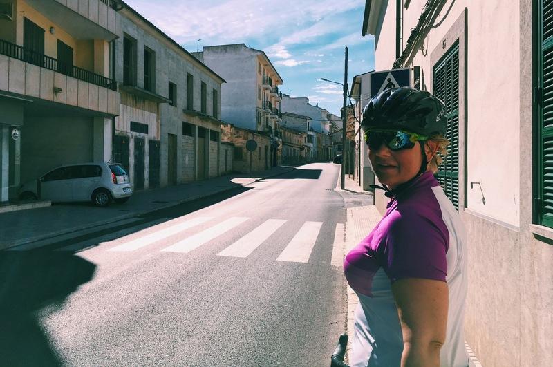 Skarpt ljus och motljus. Kvinna i cykelhjälm på en tom gata.