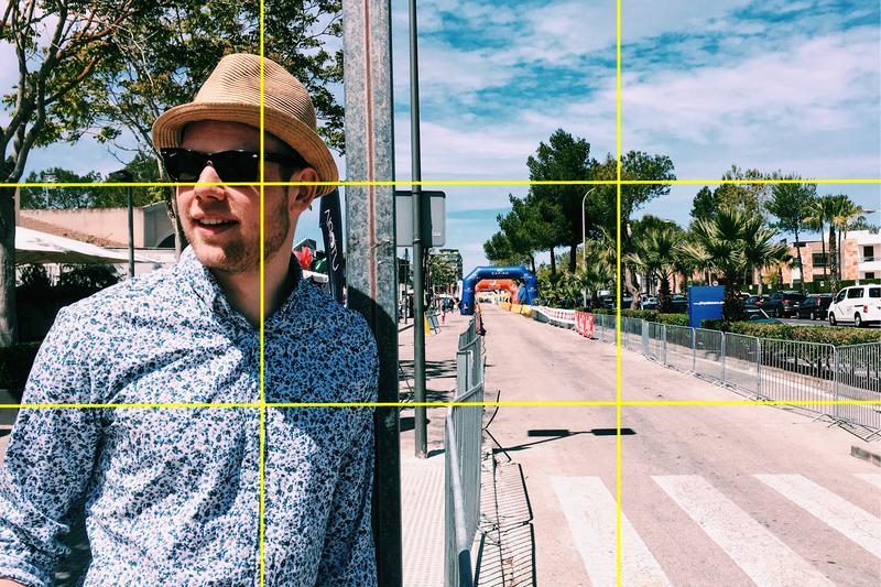 Gyllene snittet. Kille i skjorta, hatt och solglasögon vid en avstängd väg.