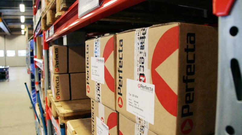 Kartonger med Perfectas pumpar i står på en hylla i hämtlagret.
