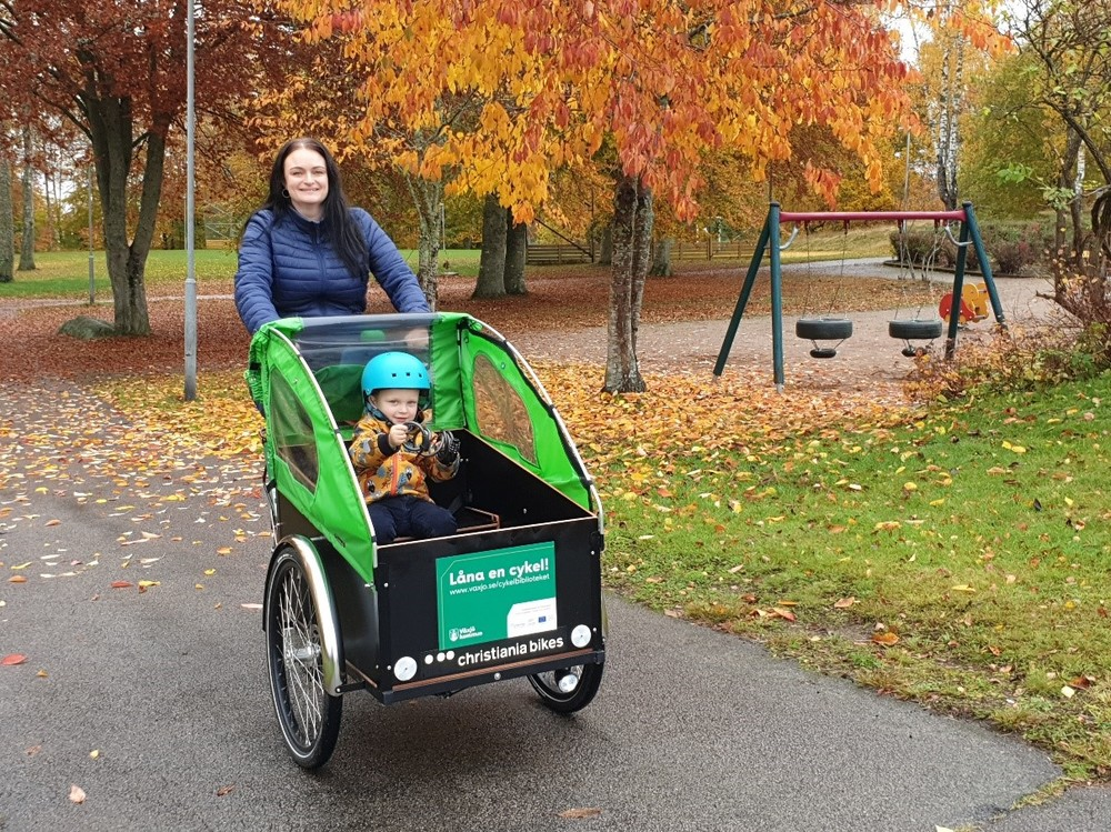 Ida and her child in a cargo bike driving through a park.