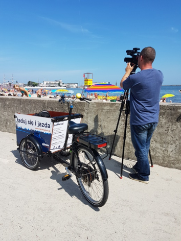 A man filming a beach with a cargo bike at his side.