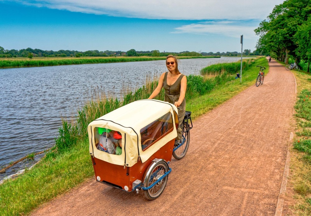 Lara driving a cargo bike by a canal.