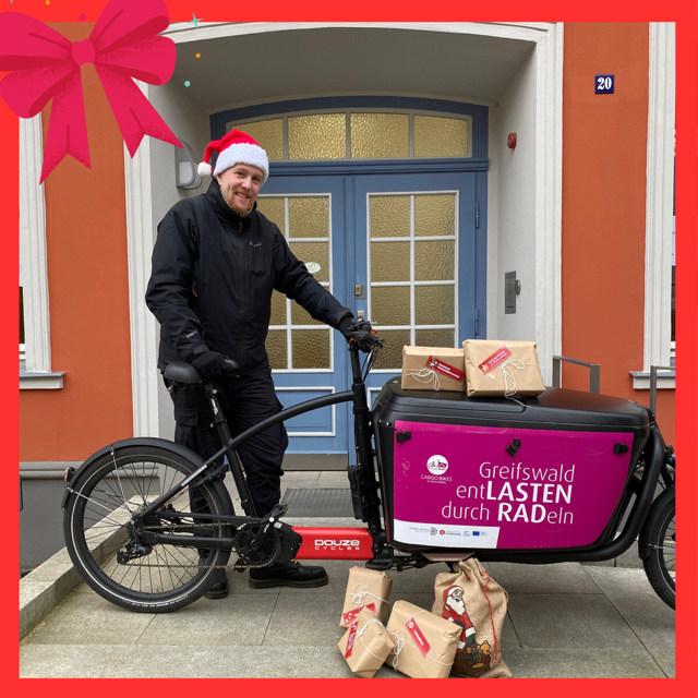 Man with Santa Claus hat and a cargo bike with wrapped packages.