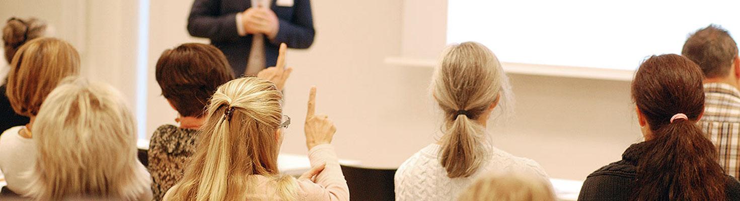 Bild på personer som lyssnar på föreläsare/utbildare i konferenslokal.