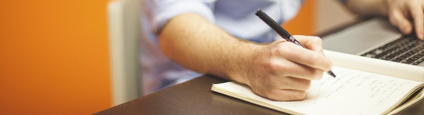Bild på en hand som skriver i en bok, andra handen på ett tangentbord.