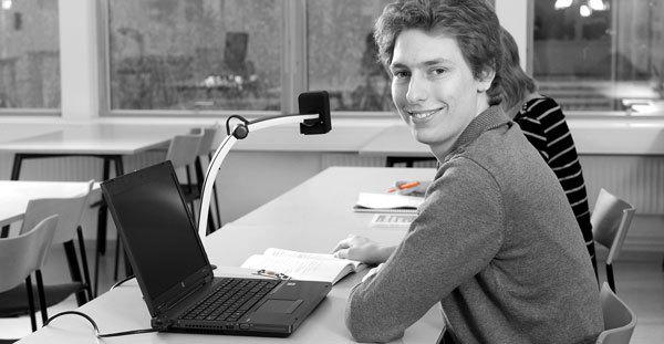 Bild på studerande med laptop och tillhörande MagniLink S Computer läskamera.