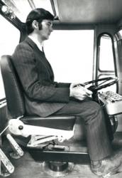 Kostymklädd man i förarhytten på en entreprenadmaskin från Ljungby maskin.