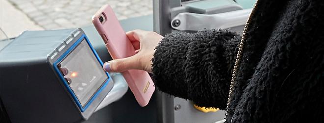 Mobiltelefon med appbiljett hålls upp mot en biljettläsare ombord på bussen