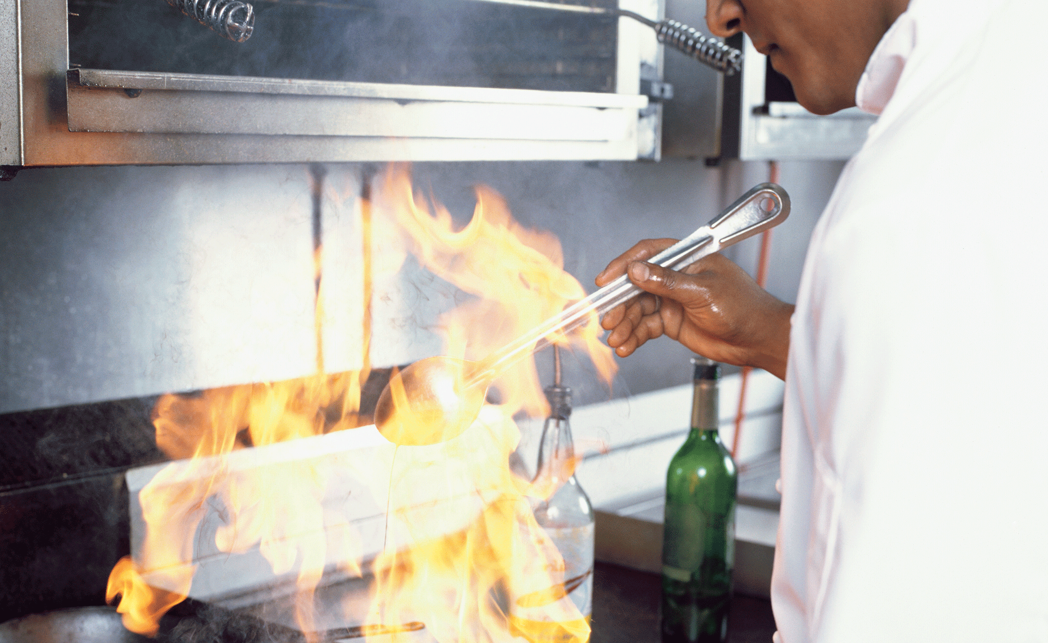 Kock i storkök som flamberar