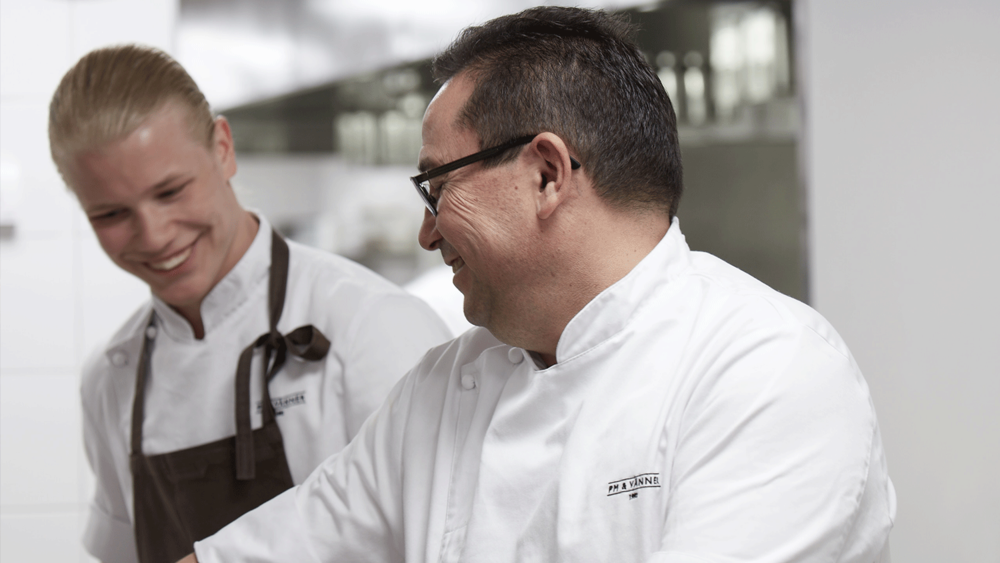 two male chefs in a restaurant kitchen laughing
