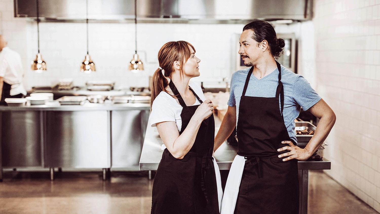 Man och kvinna klädda i förkläden står i storkök