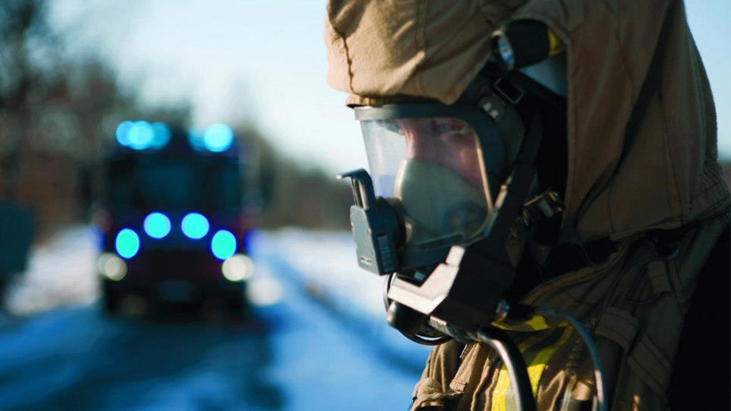firefighter with smoke diving equipment in front of a firetruck
