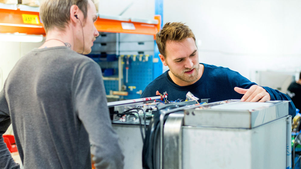 two male technicians solving a problem on a dishwasher