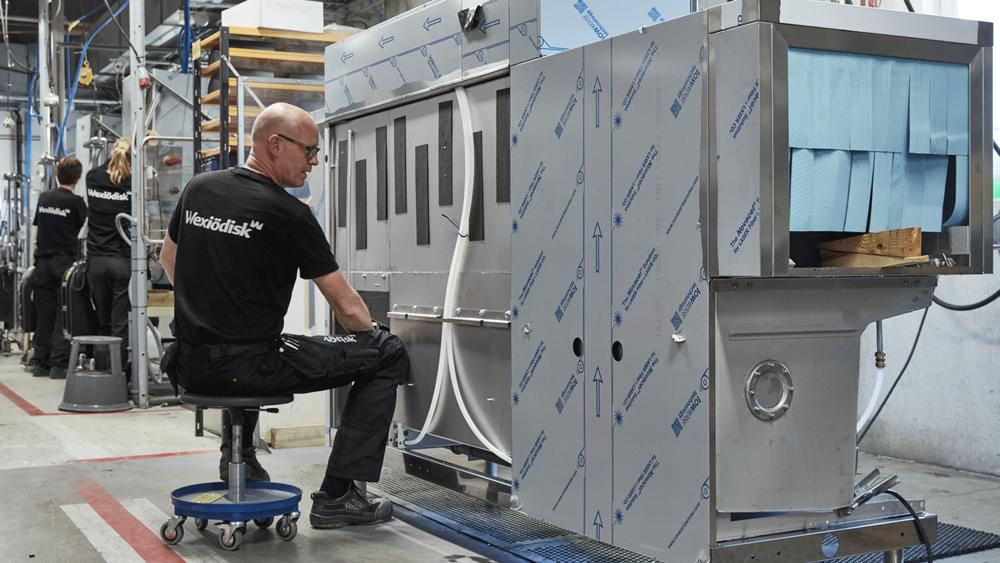 Wexiödisk tekniker som sitter framför en ny tvättmaskin i fabrik