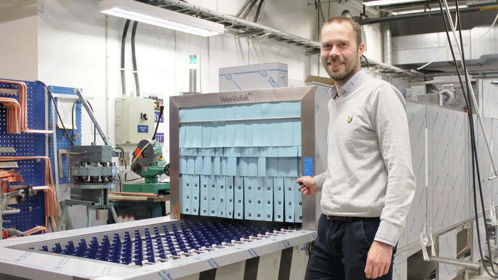 man standing in factory in front of industrial dishwasher conveyor belt