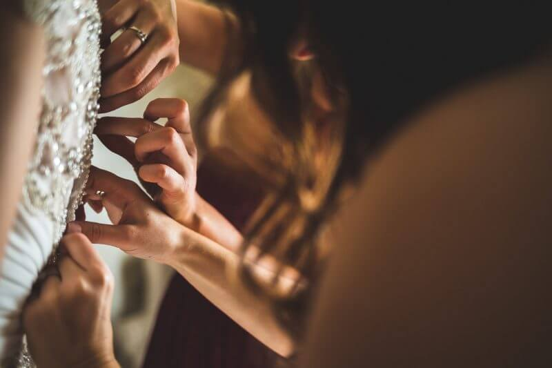 brides dress being fastened by bridesmaids