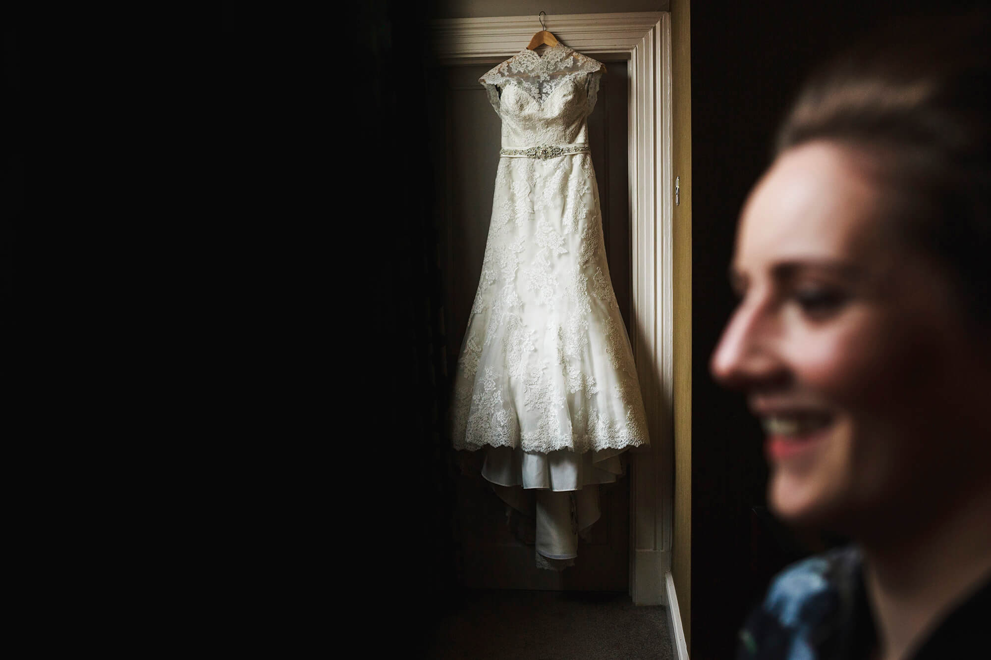 brides gets ready with her dress hanging in background