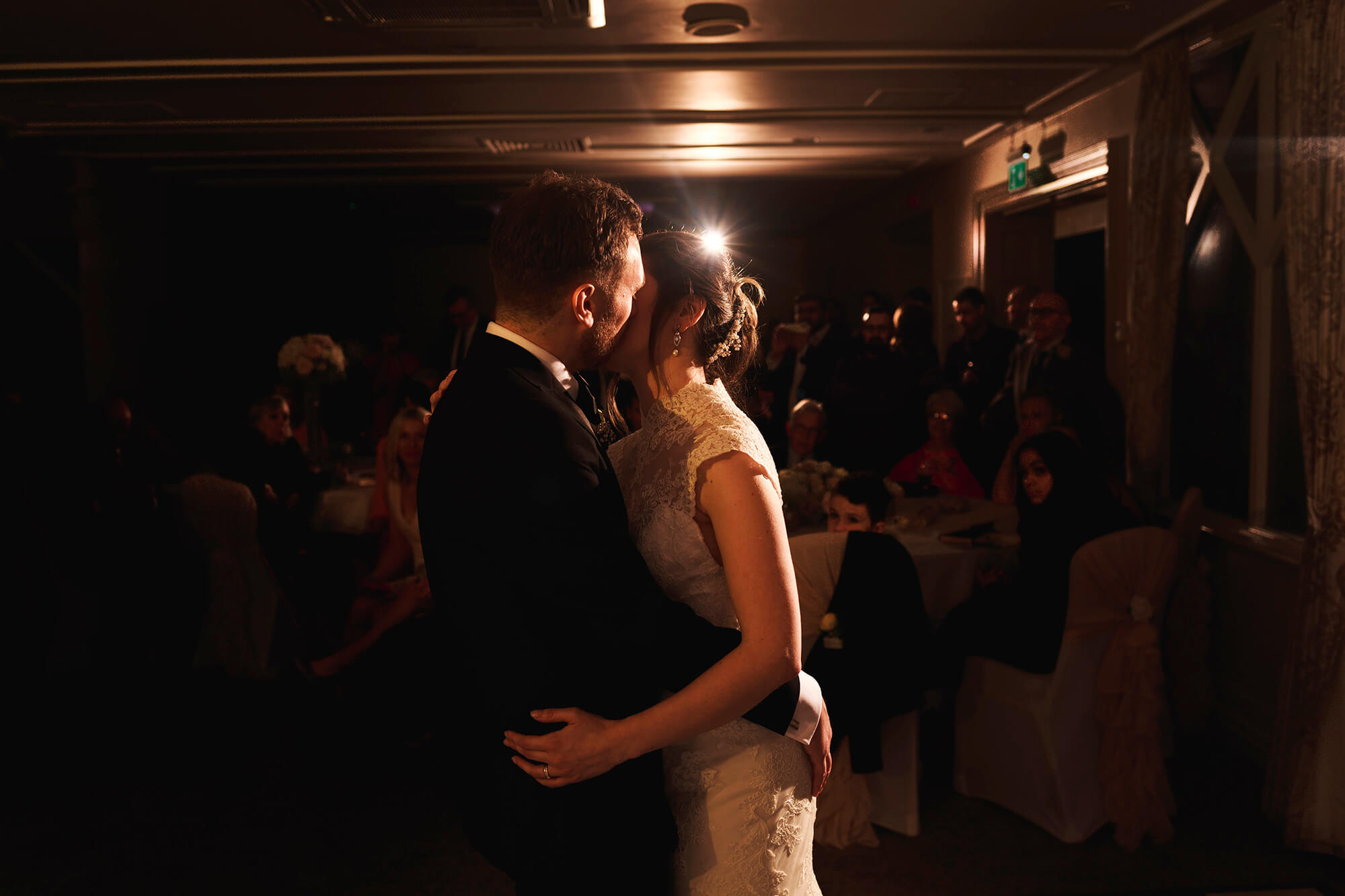 a kiss during the first dance at manor wedding