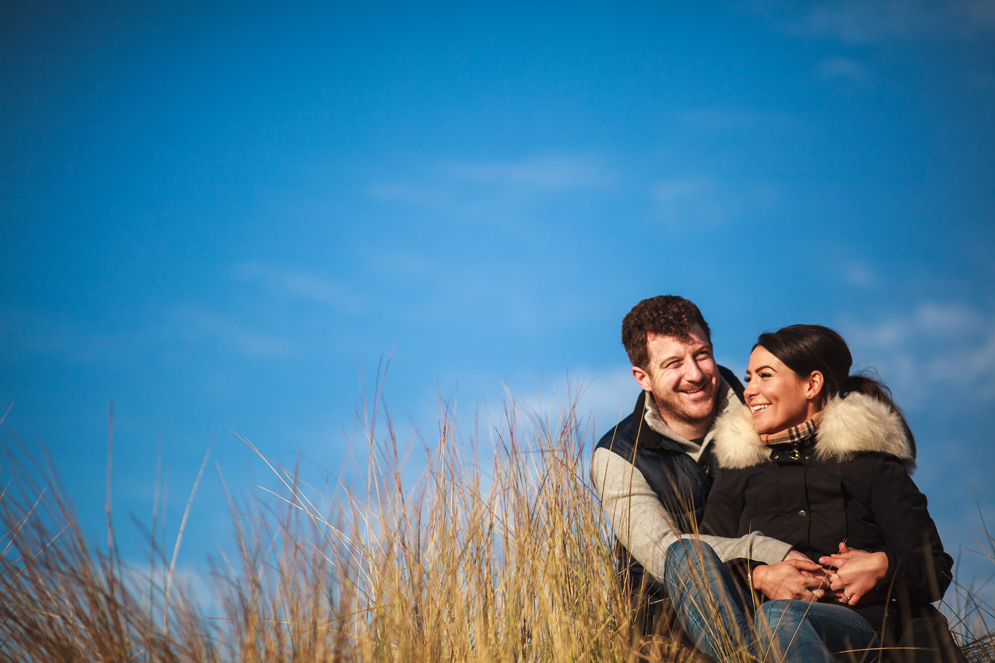 couple sat in the sand dunes in the north west