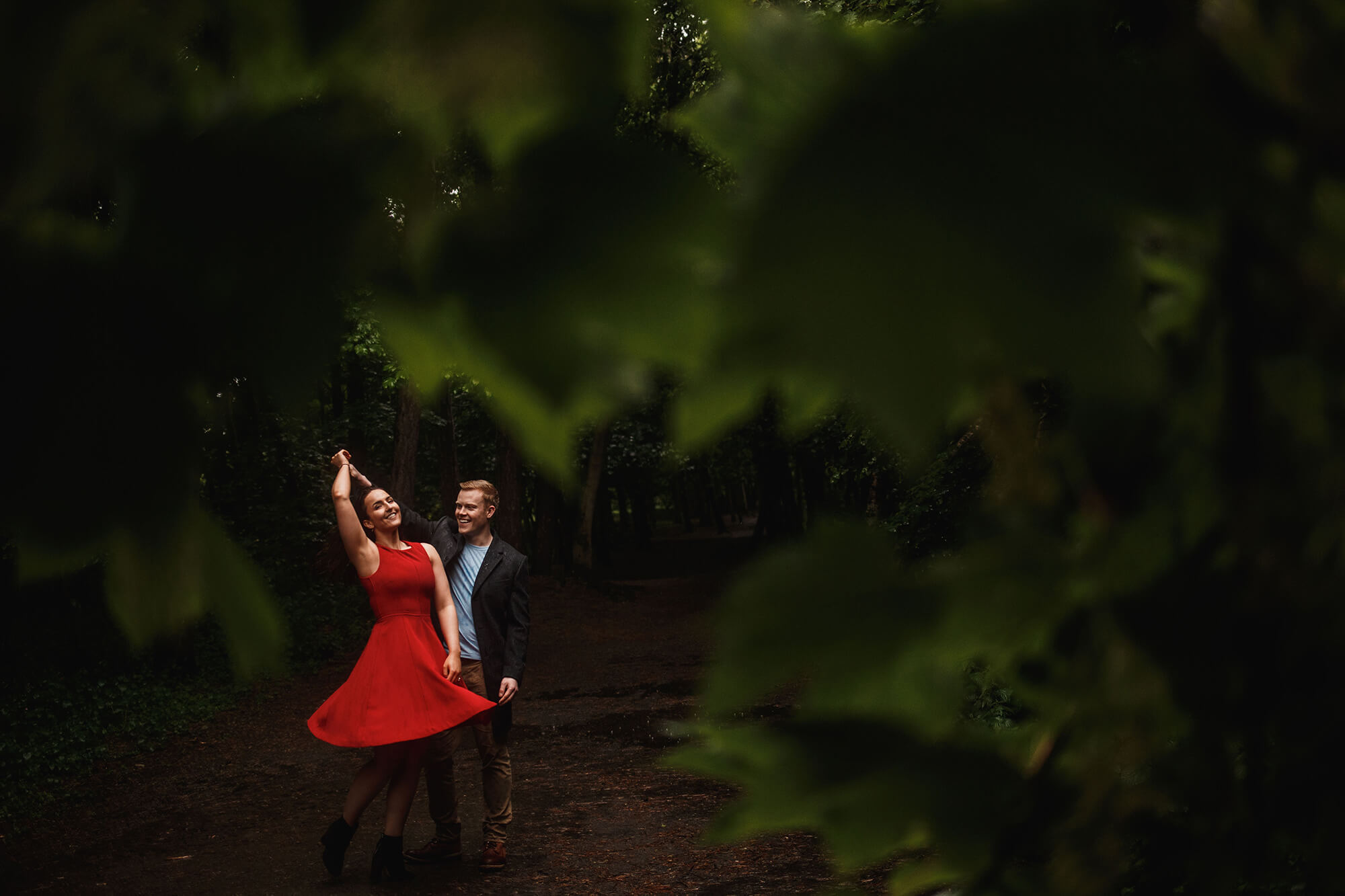 twirling girl in red dress through trees