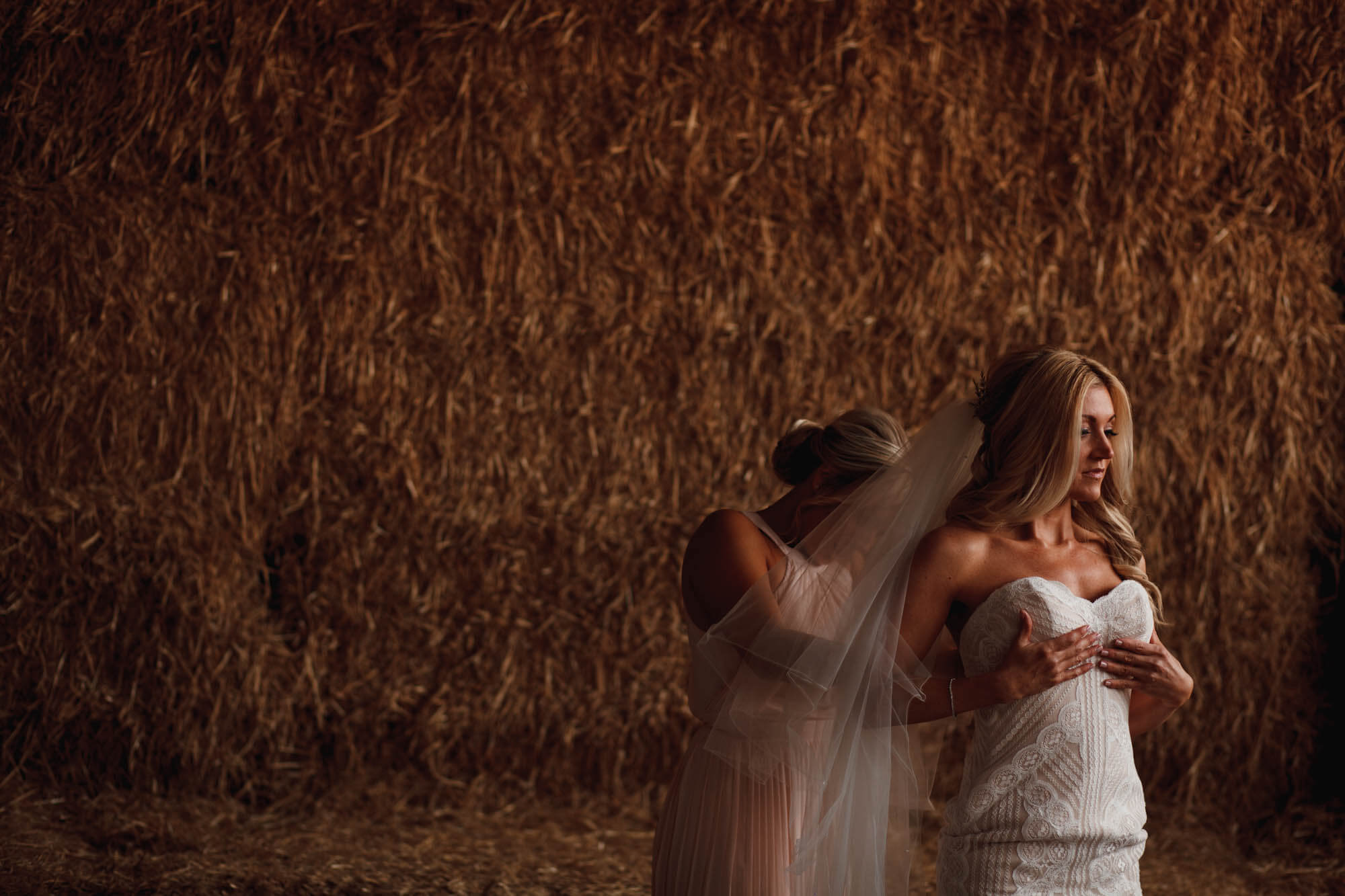 barn wedding with bride near hay bails