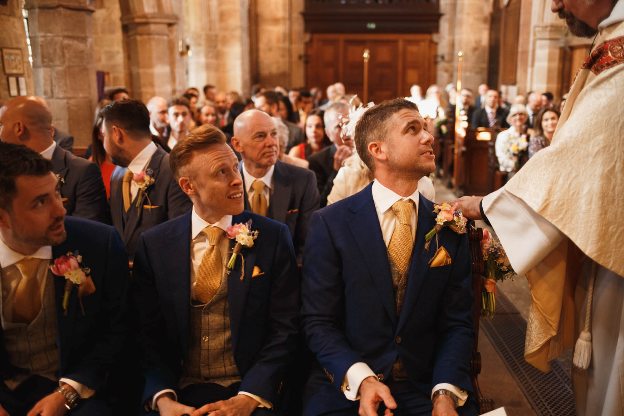 priest calms the groom in church